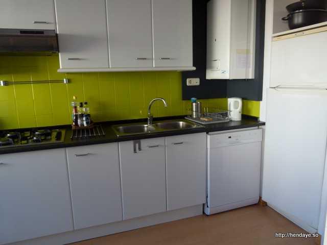 Vue de la cusine. Plaque de cuisson au gaz, Hotte aspirante. Evier 2 bacs. Lave vaisselle. Frigo avec congélateur. Chaudière au gaz. Le meubles et l'électroménager sont blancs. La crédance est vert pomme.