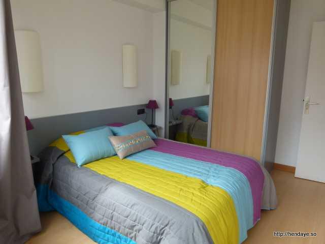 Chambre N°1 avec un lit pour 2 personnes, une grande armoir et une tête de lit.
