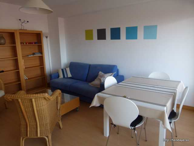 Vue du salon / séjour prise depuis l'entrée de la cuisine. Décoration sobre et contemporaine. Murs blancs