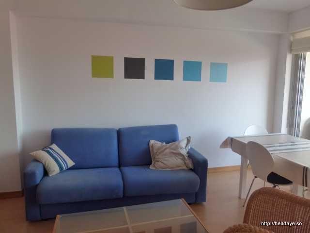 Vue de salon canapé couleur bleu . Mur blanc. Table basse et table de salle à manger avec 4 chaises