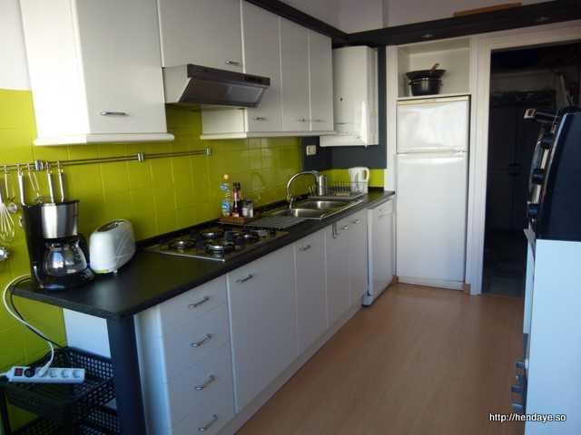 Vue de la cuisine avec dans le fond une ouverture permettant d'accéder à une arrière cuisine.