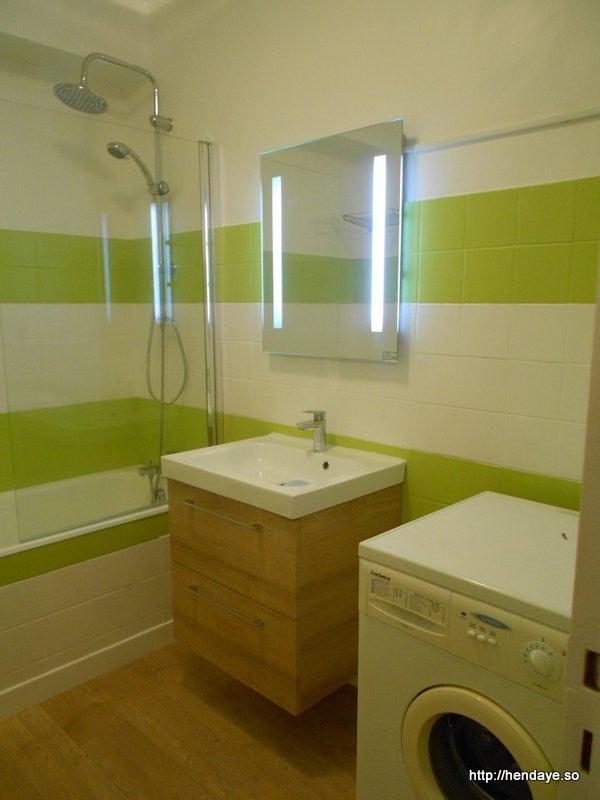 Vue de notre salle de bain couleur blanche et vert anis. Baignoire. Meuble vasque et lave linge